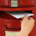 Letter being posted into postbox